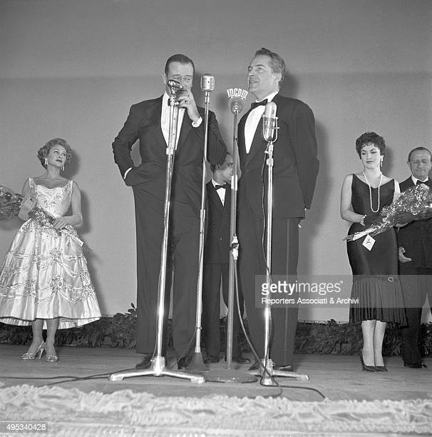 American actor John Wayne and Italian actor Rossano Brazzi at the microphone during an awarding ceremony Behind them Italian actress Gina...