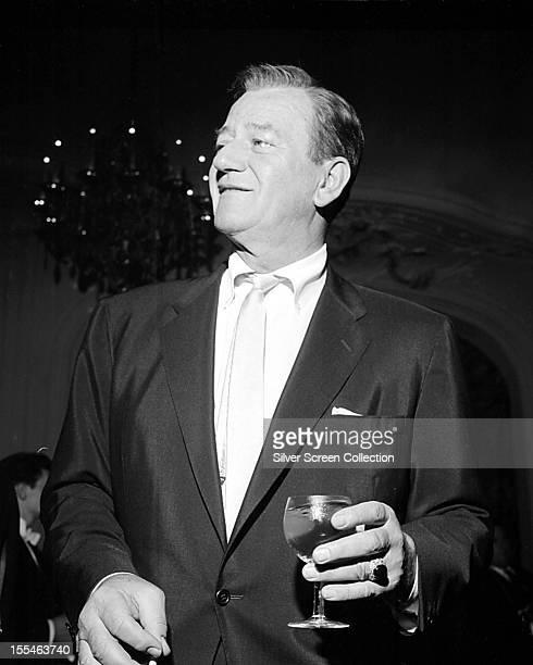American actor John Wayne holding a glass of wine at an event circa 1965