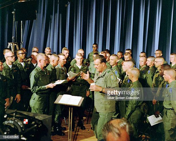 American actor John Wayne rehearsing a song with a group of US Army airborne soldiers circa 1967