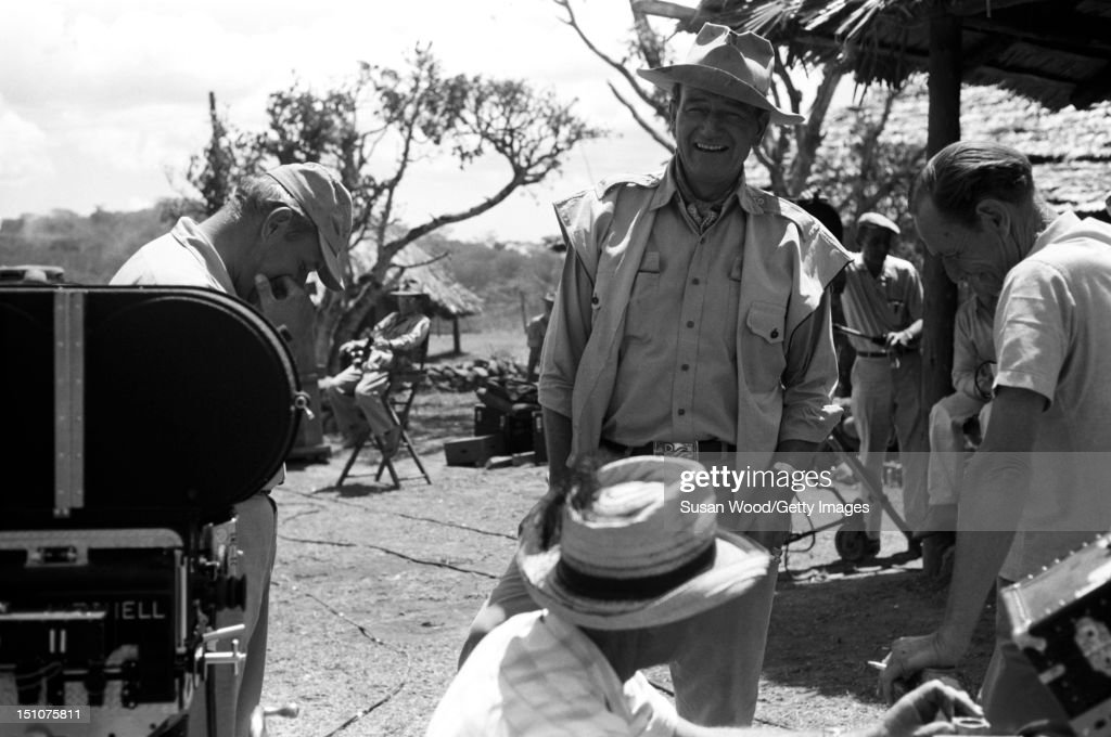 American actor <a gi-track='captionPersonalityLinkClicked' href=/galleries/search?phrase=John+Wayne&family=editorial&specificpeople=69997 ng-click='$event.stopPropagation()'>John Wayne</a> (1907 - 1979) (center) shares a laugh with others during a break in the filming of 'Hatari!' (directed by Howard Hawks), Tanzania, 1962.