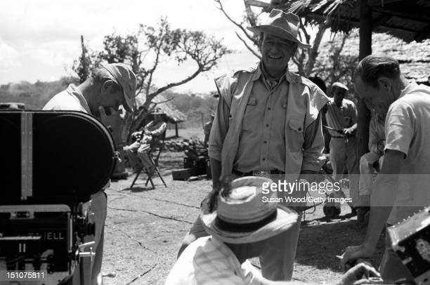 American actor John Wayne shares a laugh with others during a break in the filming of 'Hatari' Tanzania 1962