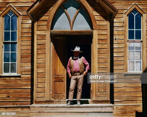 American actor John Wayne stands in a doorway on the set of 'Rio Lobo' 1970