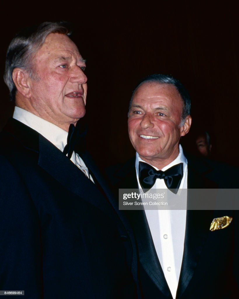 American actor John Wayne (1907 - 1979) with American singer and actor Frank Sinatra (1915 - 1998) at a social event, circa 1970.