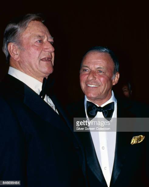 American actor John Wayne with American singer and actor Frank Sinatra at a social event circa 1970