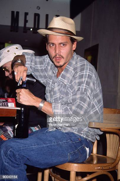 American actor Johnny Depp uncorks a bottle of wine on a podium in the atrium of the Times Square Virgin Megastore New York New York May 21 1998...