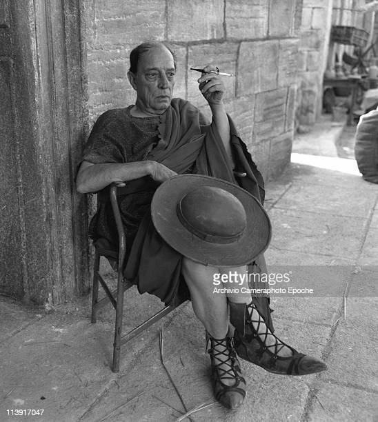American actor Joseph 'Buster' Keaton wearing a roman armor and smoking a cigarette resting during the shooting of ' A Funny Thing Happened on the...