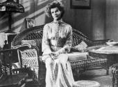 American actor Katharine Hepburn sits on a wicker lounge in a still from the film adaptation of Eugene O'Neill's play 'Long Day's Journey Into Night'...
