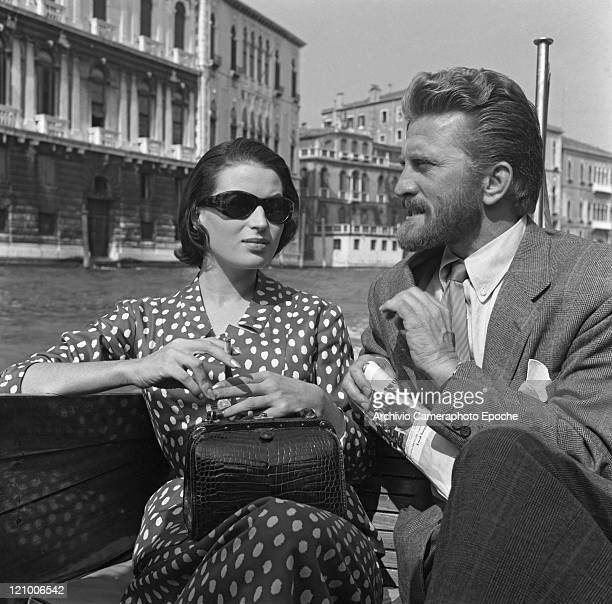 American actor Kirk Douglas wearing a suit and a tie sitting on a water taxi next to Silvana Mangano wearing a polkadotted dress and sunglasses...