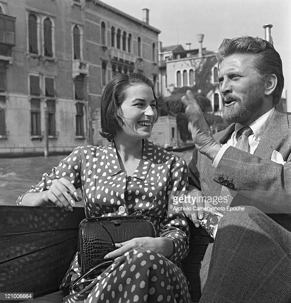American actor Kirk Douglas wearing a suit and a tie sitting on a water taxi next to Silvana Mangano wearing a polkadotted dress holding a handbag...