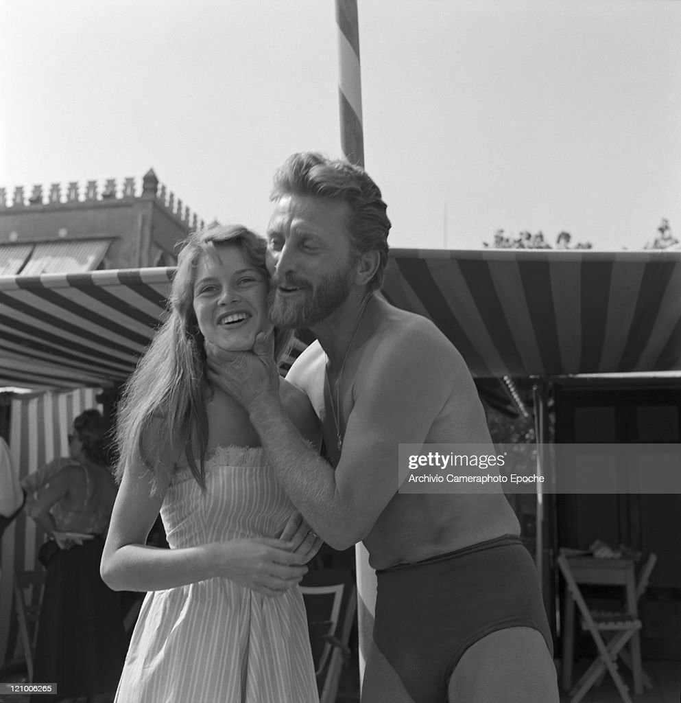 American actor Kirk Douglas wearing a swiming suit and a necklace chainlet portrayed with the actress Helene Portello on the Excelsior Hotel beach...