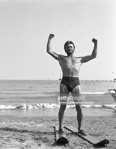 American actor Kirk Douglas wearing a swimming suit and a necklace chainlet portrayed while wearing a pair of waterski on the Lido beach Venice 1953