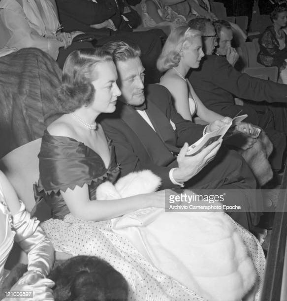 American actor Kirk Douglas wearing a tuxedo and a bow tie sitting next to the actress Olivia de Havilland wearing an evening dress and holding a...