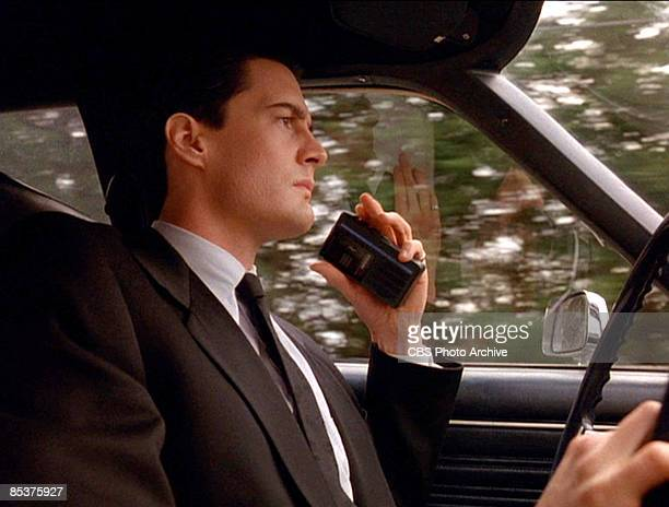 American actor Kyle MacLachlan holds a portable cassette recorder as he drives a car in a scene from the pilot episode of the television series 'Twin...
