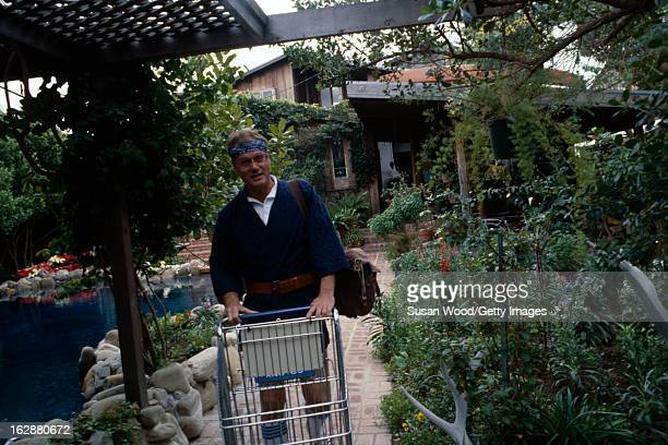 American actor Larry Hagman dressed in shorts a belted blue knit robe a blue headband and sunglasses pushes a shopping cart along a walkway on the...