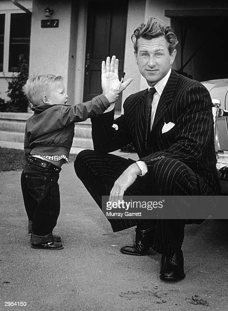 American actor Lloyd Bridges crouches in his driveway with his hand raised while his young son Jeff hands him a toothbrush outside their home Los...