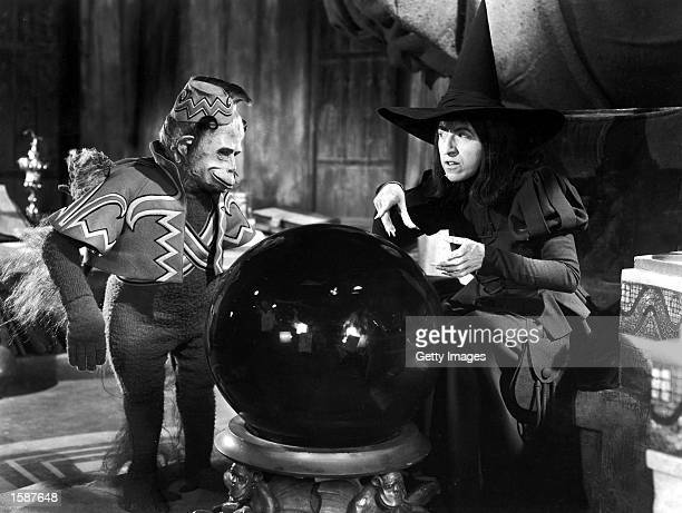American actor Margaret Hamilton and a winged monkey look into a crystal ball in a still from the film 'The Wizard of Oz' directed by Victor Fleming...