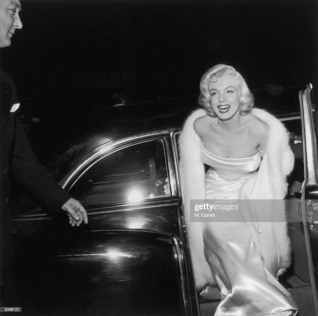 American actor <a gi-track='captionPersonalityLinkClicked' href=/galleries/search?phrase=Marilyn+Monroe&family=editorial&specificpeople=70021 ng-click='$event.stopPropagation()'>Marilyn Monroe</a> (1926 - 1962) emerges from a car, wearing a strapless white gown and white fur coat at the premiere of director Walter Lang's film 'There's No Business Like Show Business'.