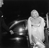 American actor Marilyn Monroe emerges from a car wearing a strapless white gown and white fur coat at the premiere of director Walter Lang's film...
