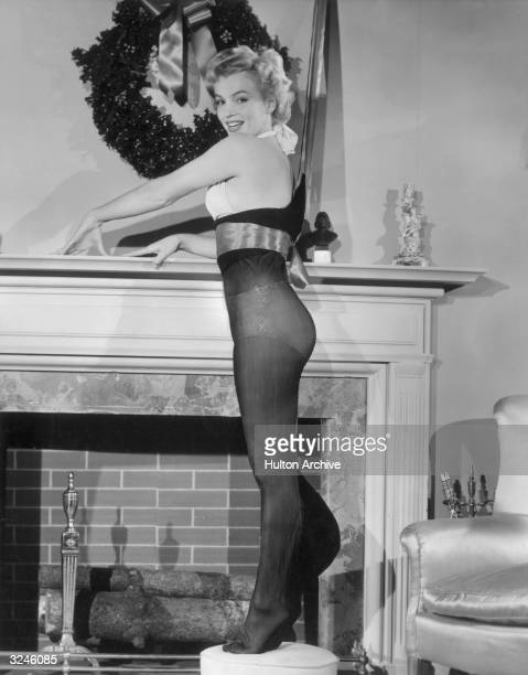 American actor Marilyn Monroe poses while standing inside an oversized nylon Christmas stocking beside a fireplace 1951 Monroe wears a twopiece...