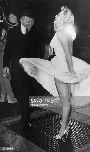 American actor Marilyn Monroe stands on a subway grate and laughs as the wind blows the skirt of her white halter dress next to Austrianborn director...