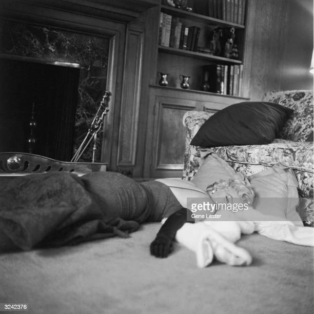 American actor Marilyn Monroe wearing a lace evening dress and long gloves lies in front of a fireplace on her fur wrap