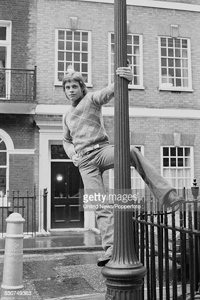 American actor Mark Hamill who plays the character of Luke Skywalker in the feature film Star Wars pictured standing on a lamp post in London on 13th...