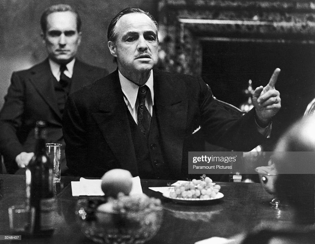 American actor Marlon Brando gestures at a table while American actor Robert Duvall sits behind him in a still from the film, 'The Godfather,' directed by Francis Ford Coppola and based on the novel by Mario Puzo.