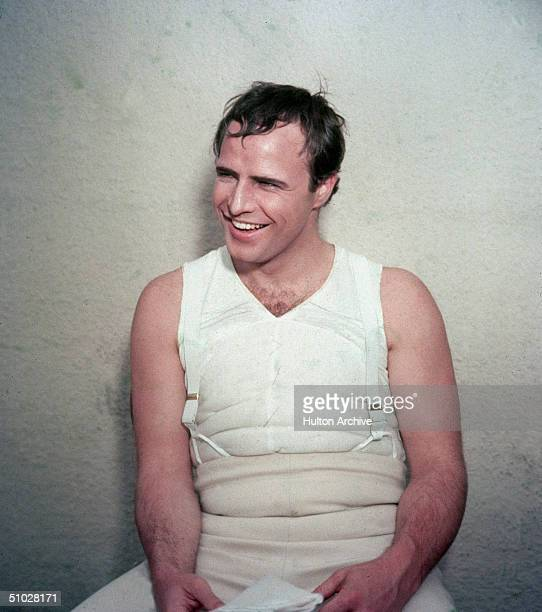 American actor Marlon Brando laughs while wearing body padding for his role as French emperor Napoleon Bonaparte in the film 'Desiree' directed by...