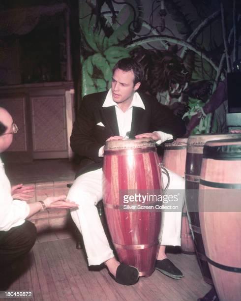 American actor Marlon Brando playing a conga drum at his home circa 1955
