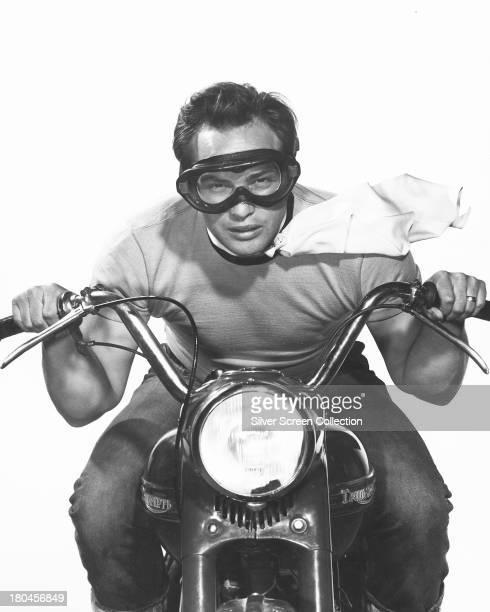 American actor Marlon Brando posing on a Triumph motorcycle circa 1953