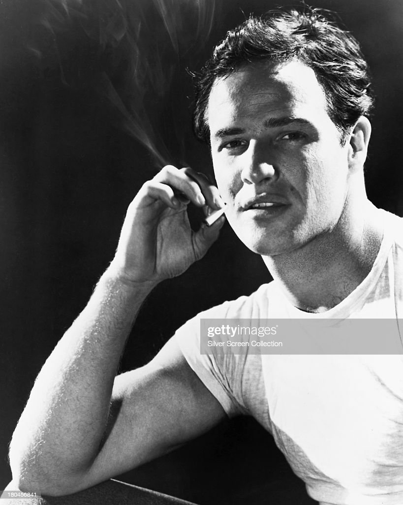 American actor <a gi-track='captionPersonalityLinkClicked' href=/galleries/search?phrase=Marlon+Brando&family=editorial&specificpeople=85897 ng-click='$event.stopPropagation()'>Marlon Brando</a> (1924 - 2004) wearing a white T-shirt and smoking a cigarette, circa 1950.