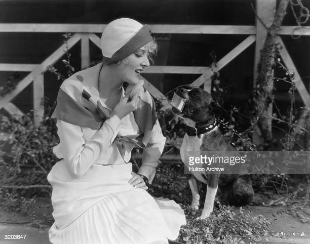American actor Mary Nolan seated on the ground and powdering her chin while looking into a compact mirror held for her in the mouth of a dog