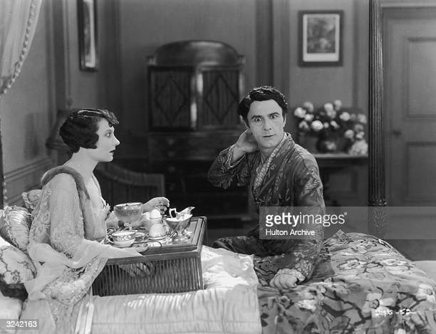 American actor Maude George sits up with a breakfast tray in her lap while Australianborn actor Andre Beranger sits at the edge of her bed in a still...