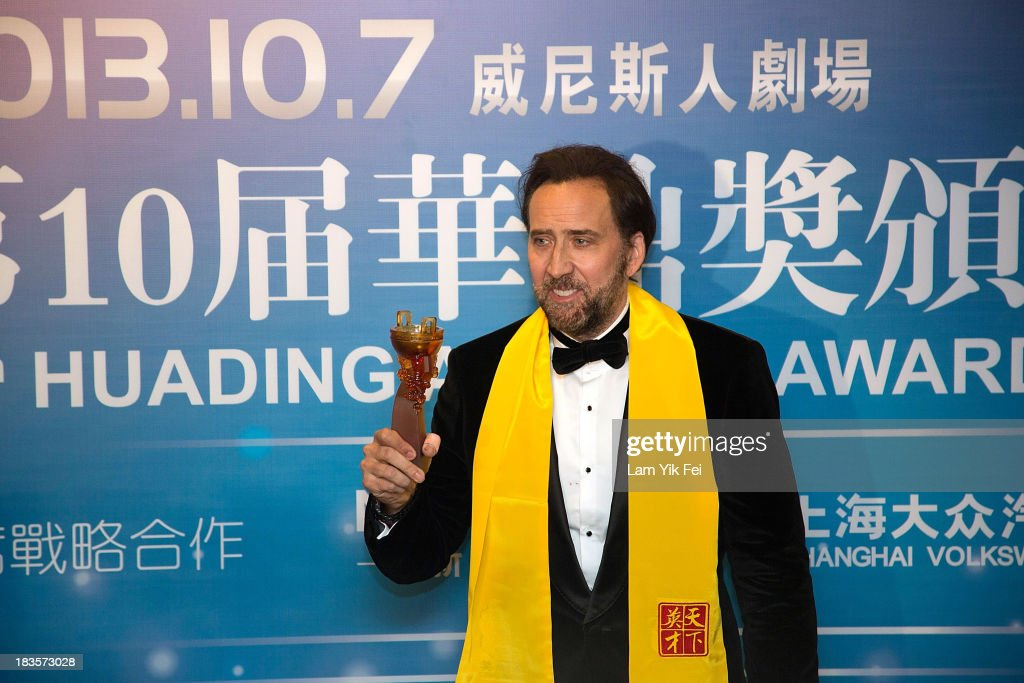 American actor Nicolas Cage poses after winning Best Global Actor in Motion Picture at the 2013 Huading Awards ceremony at The Venetian on October 7, 2013 in Macau, Macau.