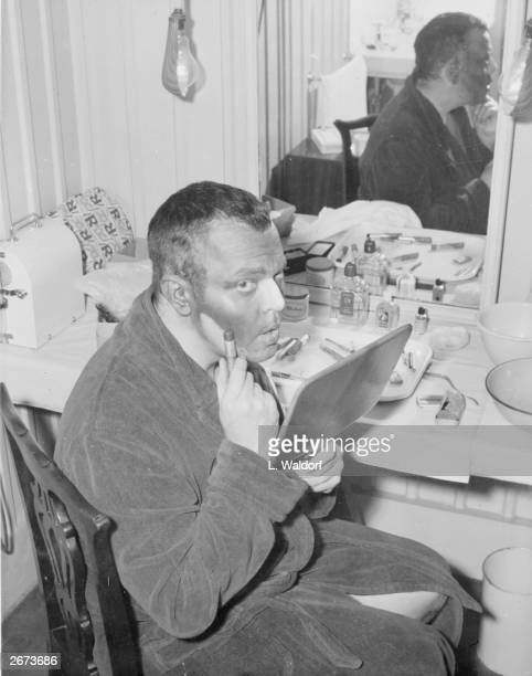 American actor Orson Welles blacks up his face for the role of William Shakespeare's Othello