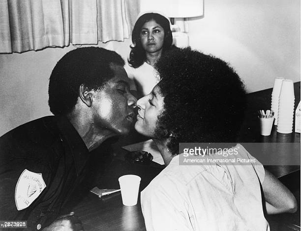 American actor Pam Grier leans over to kiss an unidentified actor in a policeman's uniform in a still from the film 'Coffy' directed by Jack Hill 1973