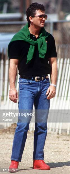 American actor Patrick Duffy with his jumper tied around his shoulders and pair of red shoes circa 1990