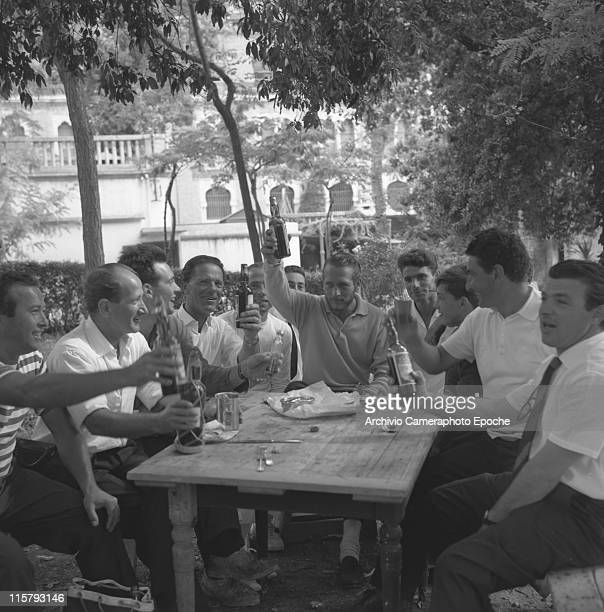American actor Paul Neuman sitting at a table in the Excelsior garden with many other men holding a bottle of beer and toasting with them Lido Venice...