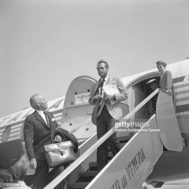 American actor Paul Newman holding papers and sunglasses getting down the stairs of an Alitalia airplane in Tessera airport Marco Polo a hostess...