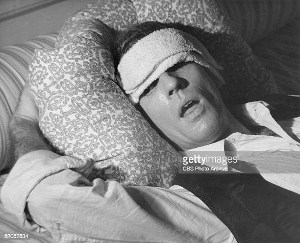 American actor Peter White lies down with a washcloth over his eyes in a scene from the movie adaptation of Mart Crowley's play 'The Boys in the...