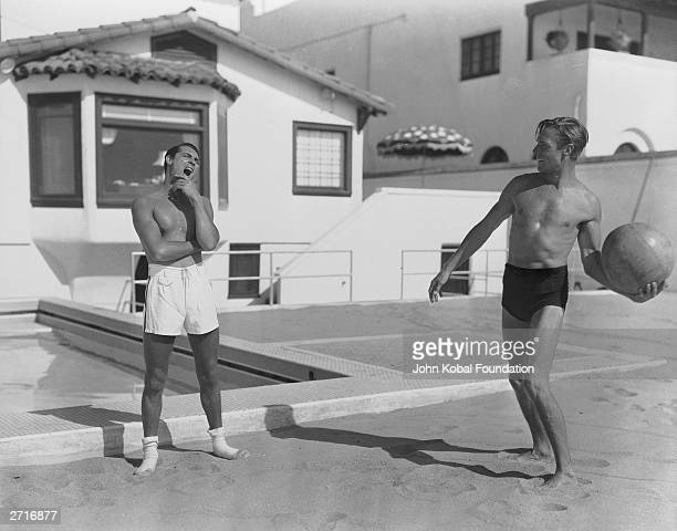 American actor Randolph Scott and British born actor Cary Grant playing with a ball at the beach house they share