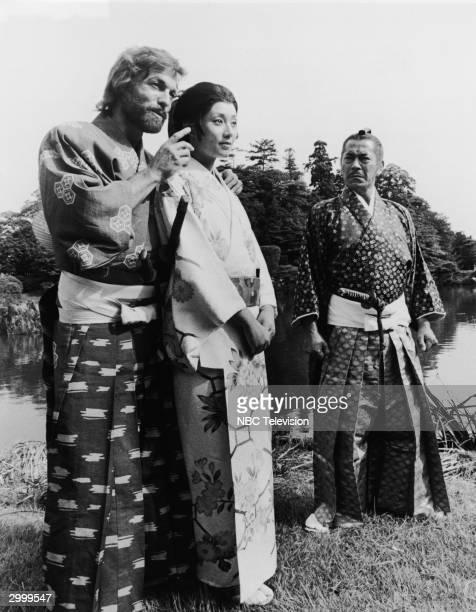 American actor Richard Chamberlain points while standing behind actor Yoko Shimada as actor Toshiro Mifune looks on form the TV miniseries 'Shogun'...