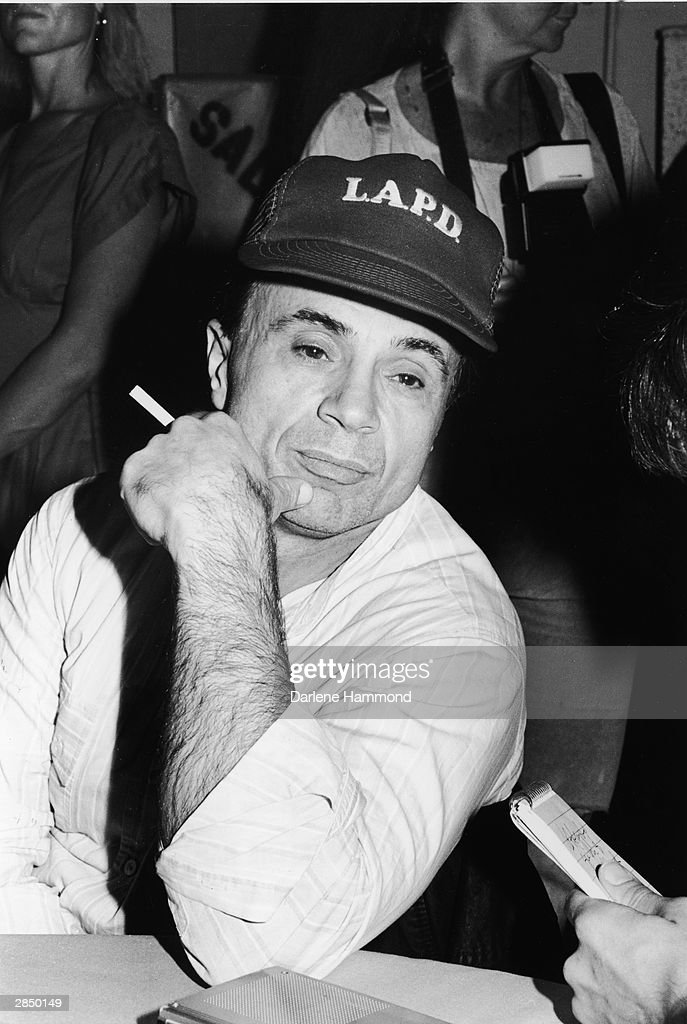 American actor Robert Blake sits holding a cigarette and wearing an LAPD baseball cap, while attending a benefit for a medical airlift to El Salvador at the Santa Monica Airport, Santa Monica, California, November 23, 1986.