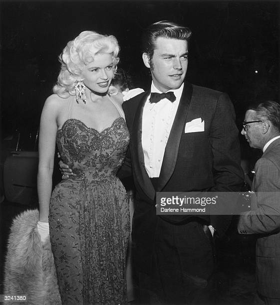 American actor Robert Wagner squints while standing with his arm around actor Jayne Mansfield's waist at the premiere of director Anatole Litvak's...
