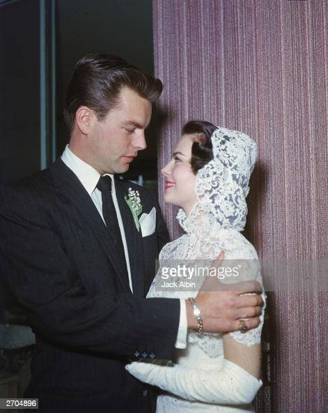 American actor Robert Wagner wearing a suit and tie with a corsage and American actor Natalie Wood wearing a white strapless wedding dress with a...