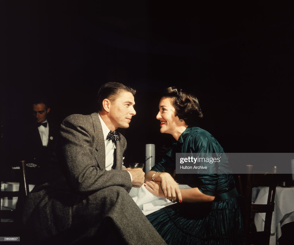 American actor Ronald Reagan and his wife Nancy Reagan gaze at one another across a table circa 1952