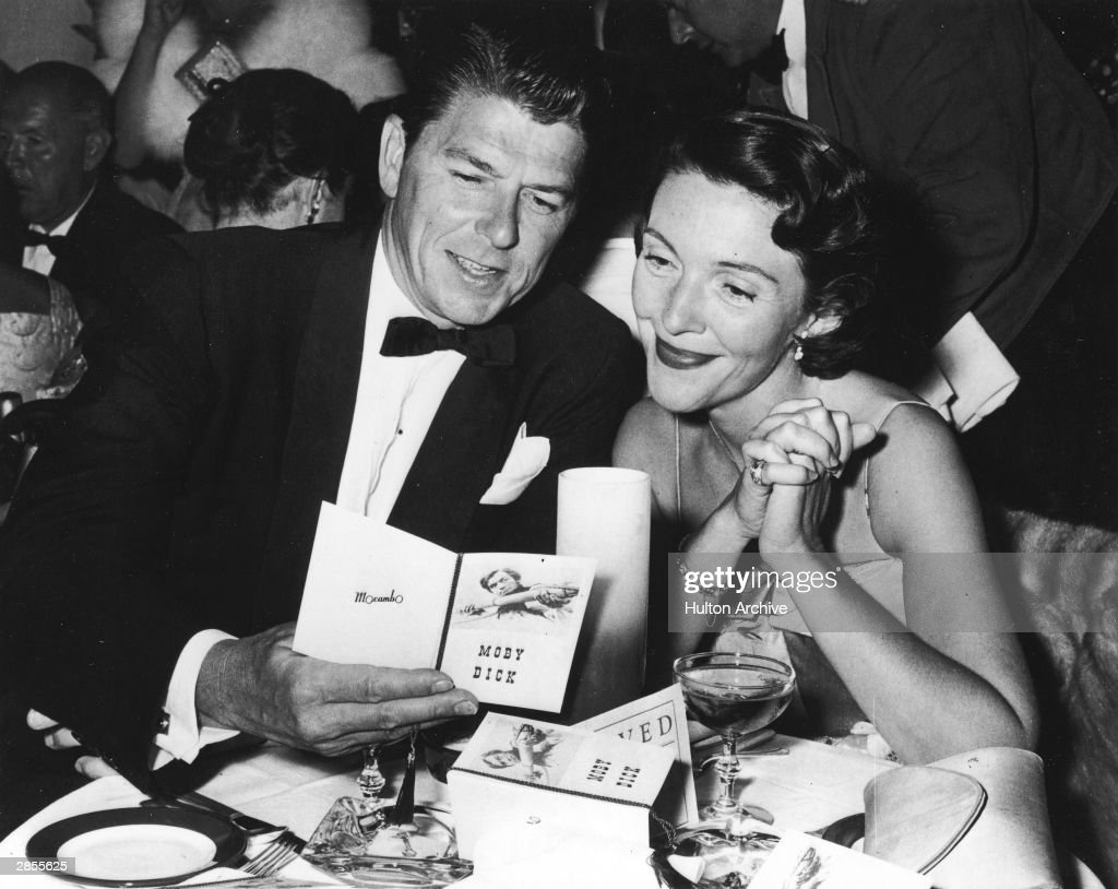 American actor Ronald Reagan and his wife Nancy Reagan sit at a restaurant table looking at a brochure at the premiere party for the film 'Moby Dick'...