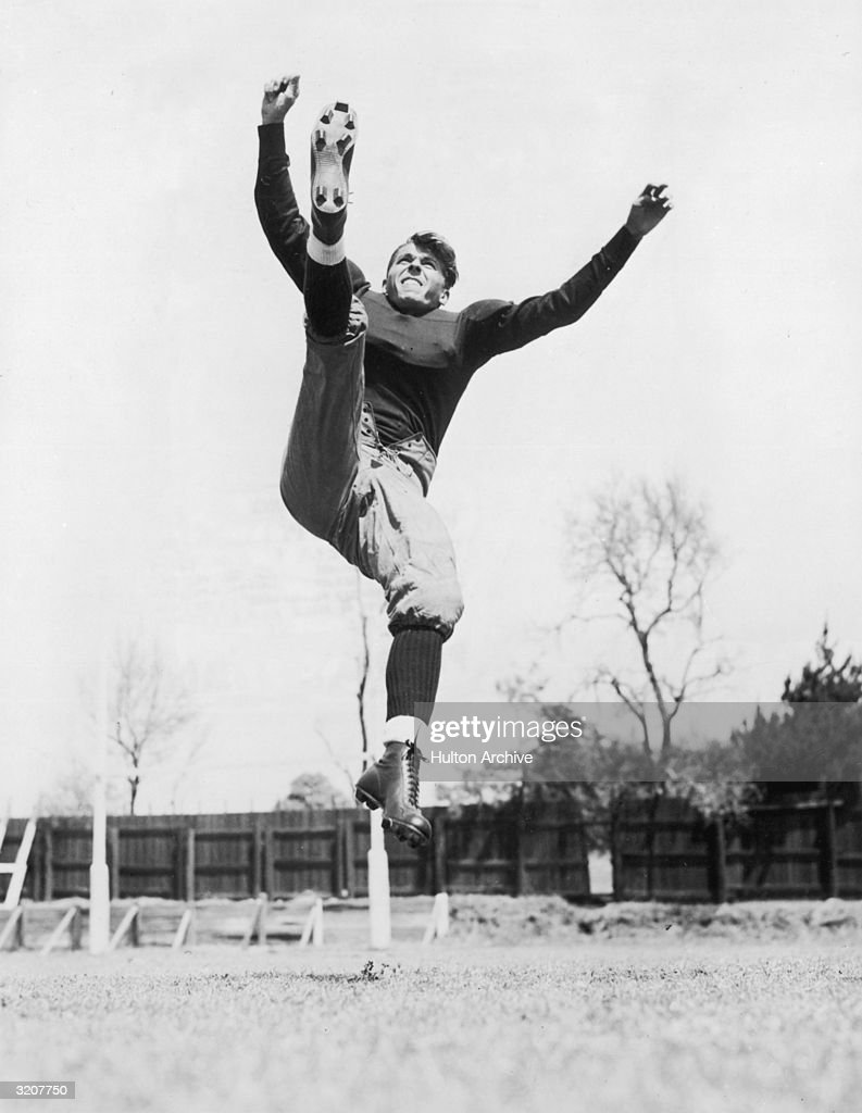 American actor Ronald Reagan dressed in a football uniform punting in midair in a movie still from director Lloyd Bacon's film 'Knute Rockne All...