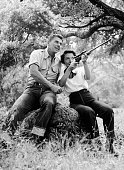 American actor Ronald Reagan watches as his wife Nancy aims a rifle while they sit on a large rock outdoors at their ranch in Malibu California Both...
