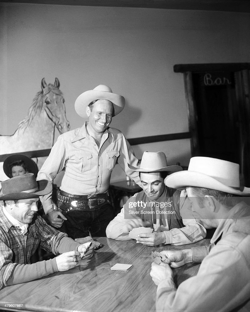 American actor Rory Calhoun playing cards with a group of men in cowboy costume circa 1955